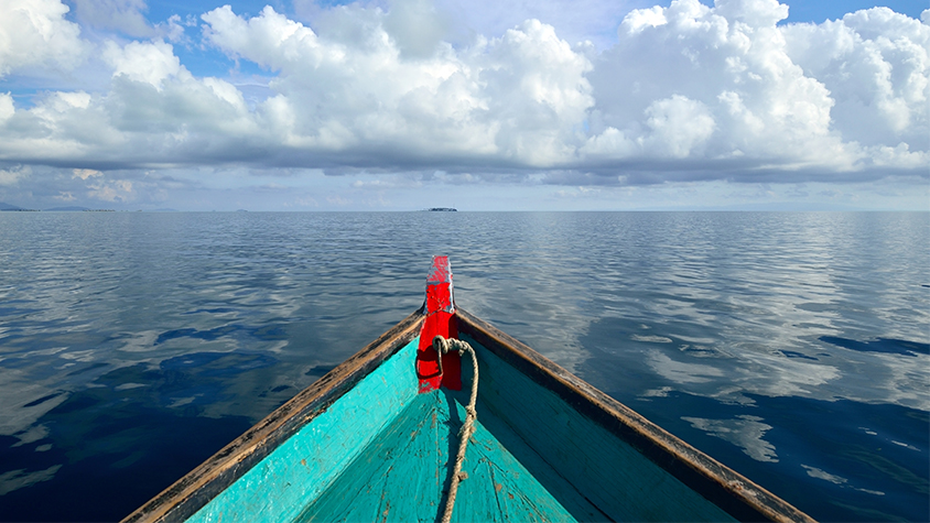 A boat is moving towards an undisclosed location in the ocean, from the boat occupant's