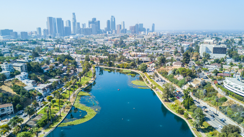 A bird's eye view of the the Los Angeles skyline and Echo Park lake and trees alongside two main highways.