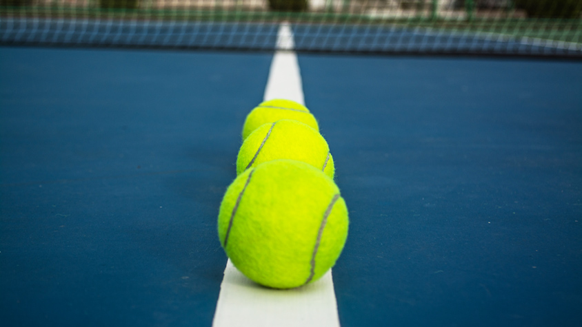 A detailed shot of three yellow tennis balls shown on a bright blue tennis court.