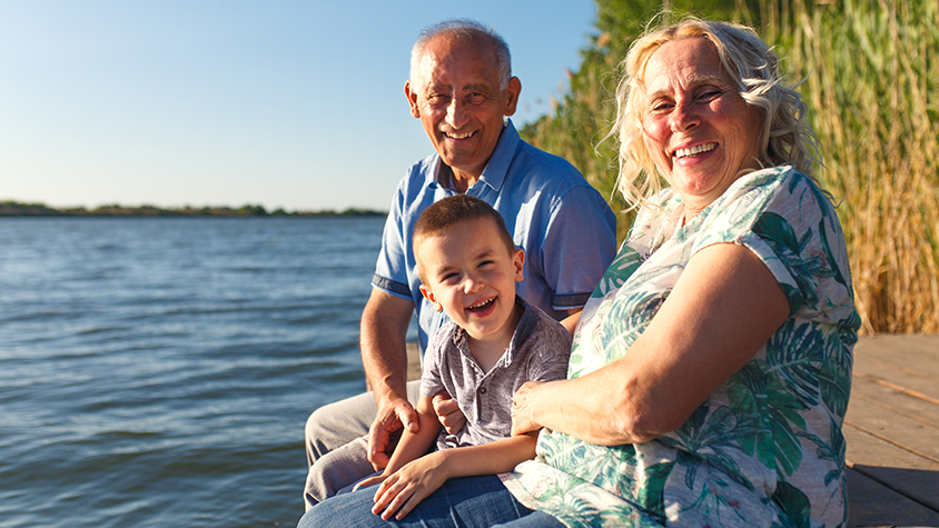 Elderly couple sits on a dock by the lake with their grandson as they all laugh.