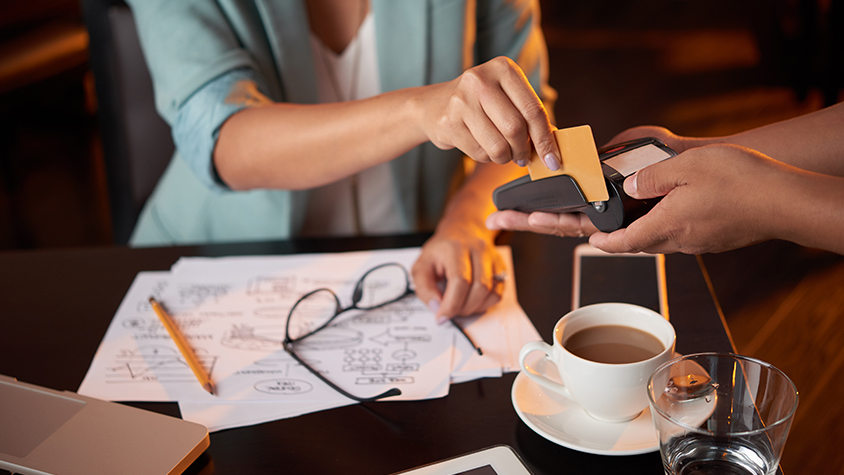 Female customer pays at coffee shop with credit card on a mobile payment system held by an employee.