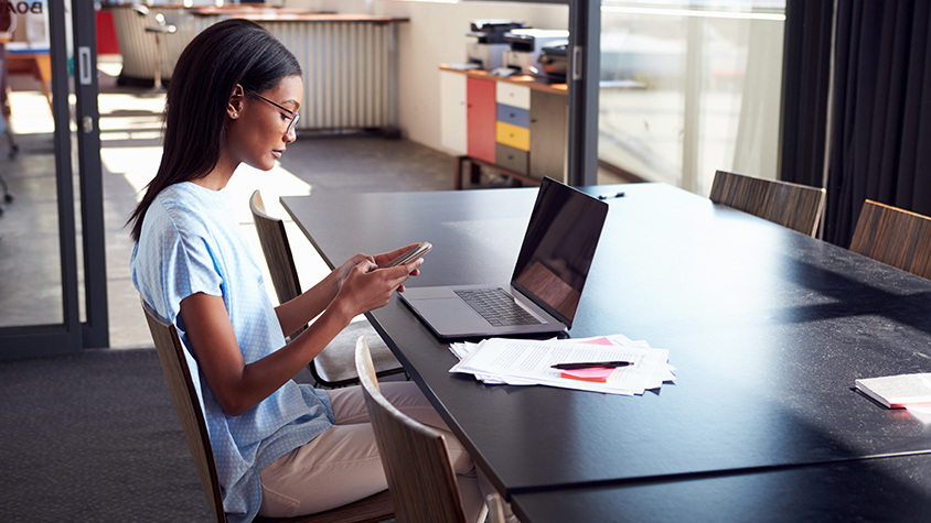 African American female sits at a desk while on smartphone with a laptop, papers, pen and post-its.