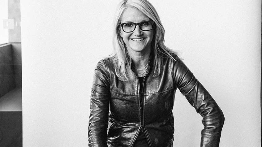 Black and white photo of Mel Robbins sit on a stool laughing in front of a blank wall.