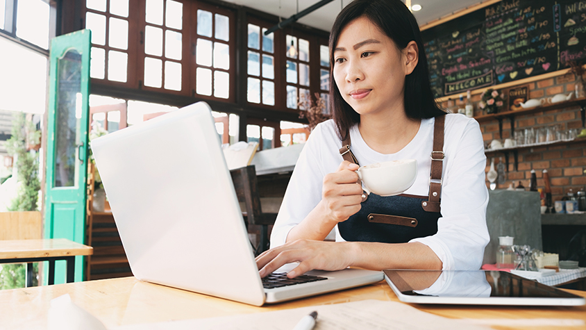 Asian, young female sits in a coffee shop while on her laptop.