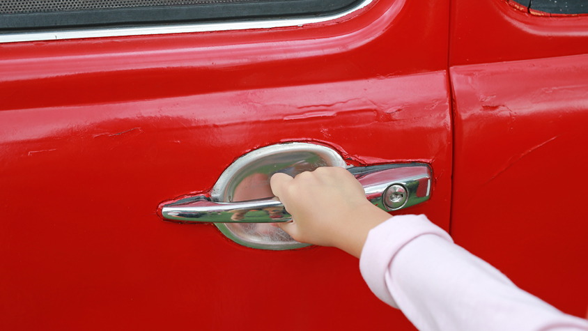 Image of a hand opening a red car door