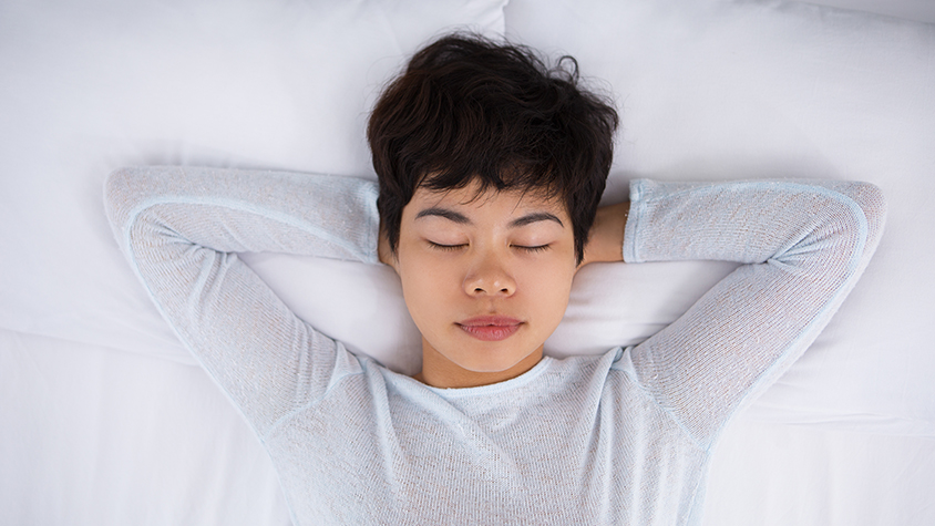 Asian girl lays on bed in a white sweater and facing the ceiling with her eyes closed.