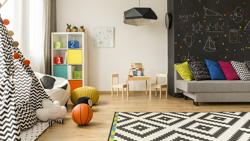 A multi-color kids playroom inside of a home including a play tent, couch and chalkboard wall.