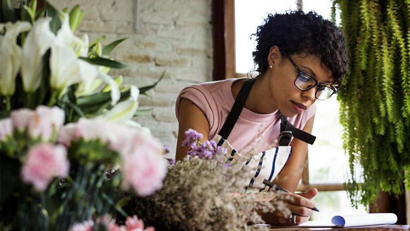 A young florist writes on a notepad in her working environment.