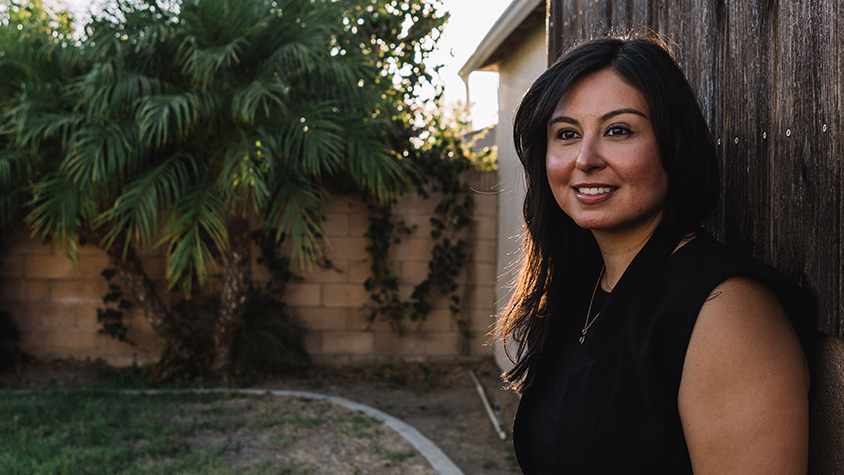 Image shows Karla Ruiz, the woman featured in this story, outside against a wooden backdrop.