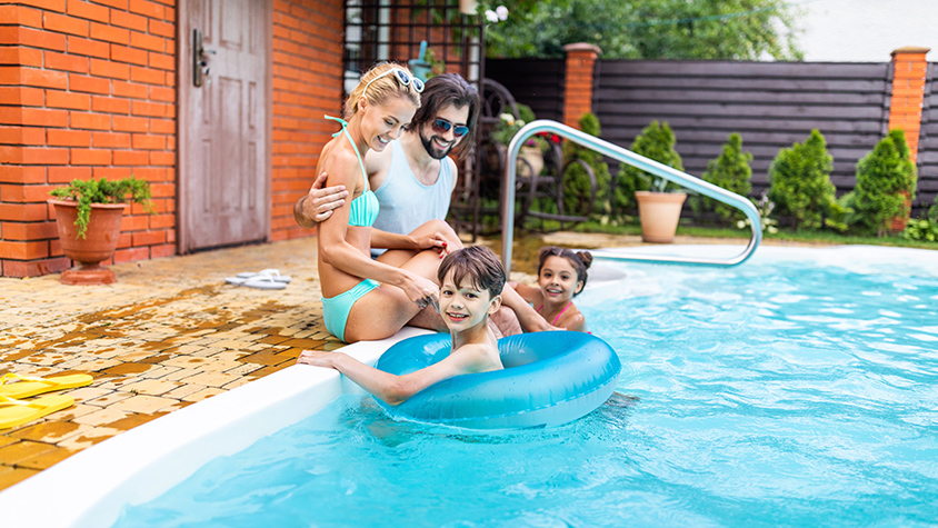 Married couple sit by the pool in their backyard while their son and daughter swim.