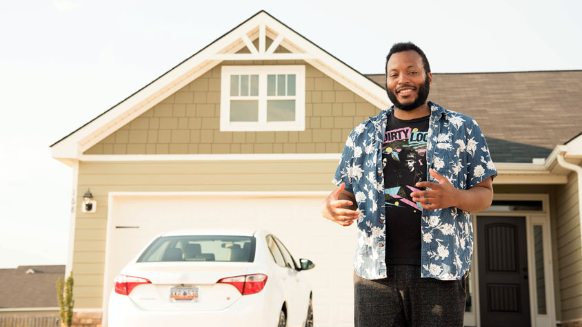 Man standing with car in front of a house