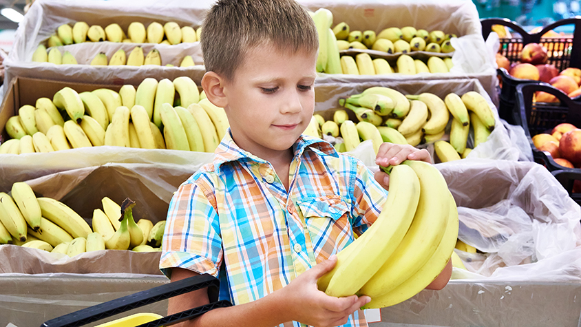 little boy holding bananas