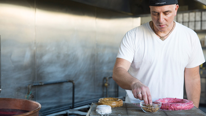 Mark Israel, founder of Doughnut Plant, is shown in his workspace creating the Ripple doughnut.