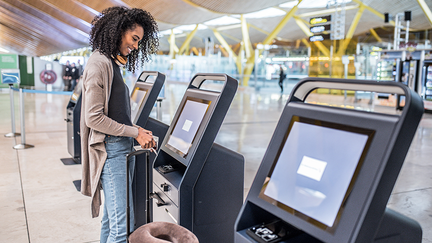 A young African-American women is at the airport checking in to her flight at a digital kiosk.
