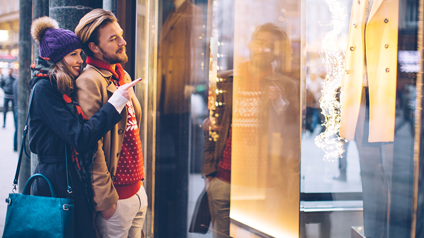 couple standing at storefront window