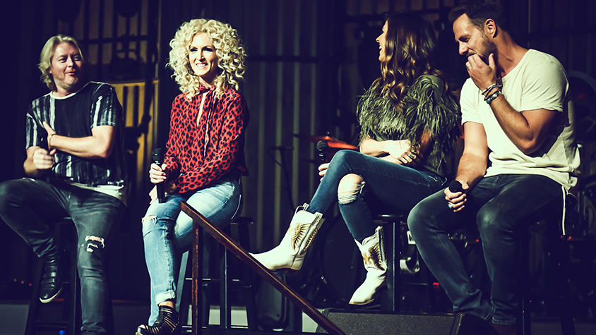 Country music stars sitting on stage panel
