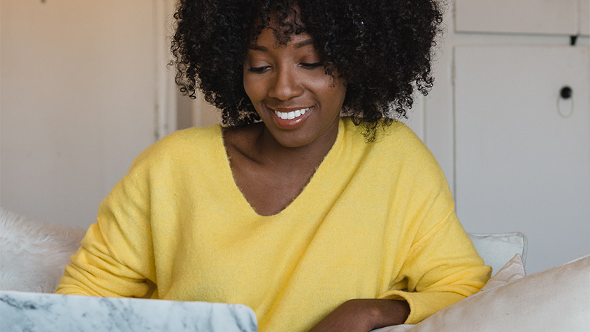 Photo of Tonya Rapley on her laptop with star illustrations to the left and right of her picture.