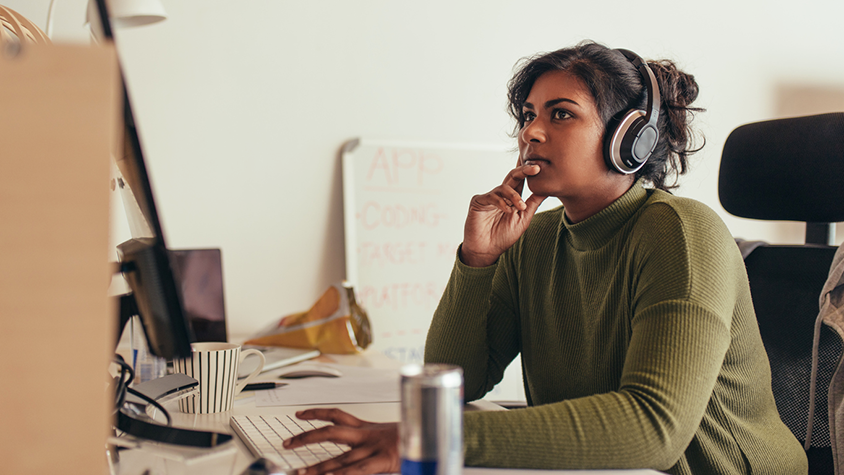Woman sitting at desk and listening on headphones