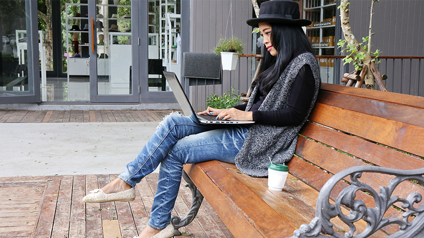 Woman sitting on bench while working on laptop