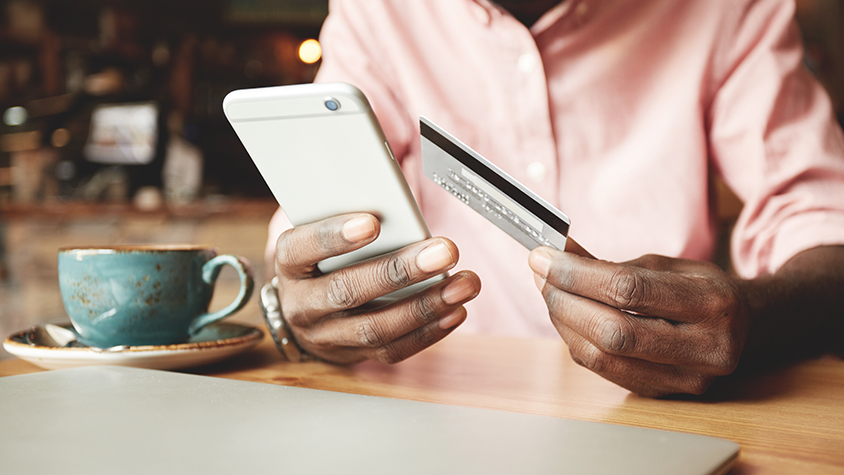 A man holding his mobile device in one hand and his credit card in the other hand.