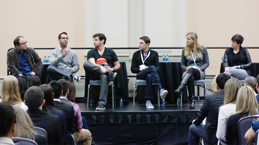 Panelists on stage at a conference