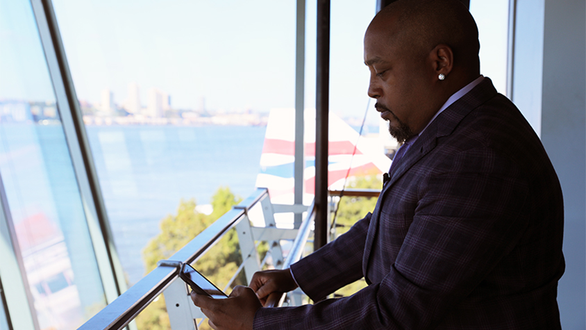 Daymond John looks at his phone while leaning up against the balcony outside of a building.